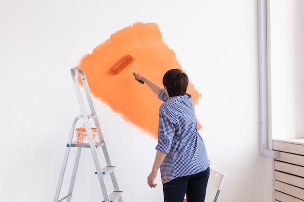 Mulher de meia-idade pintando as paredes de uma nova casa