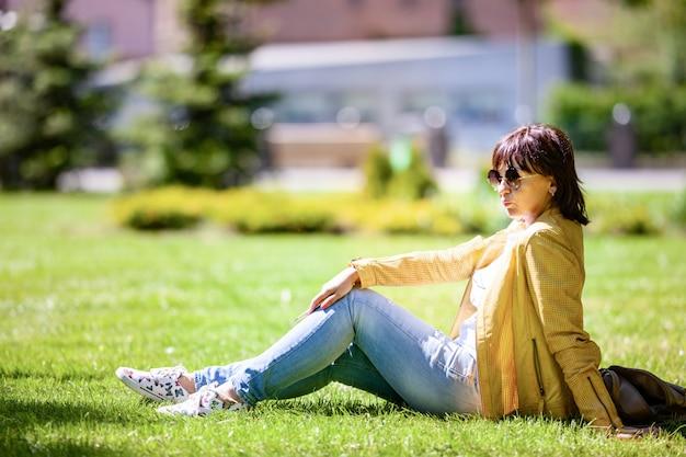 Mulher de meia-idade positiva com óculos escuros sentada em um campo de um parque e lendo um livro em um dia ensolarado de verão