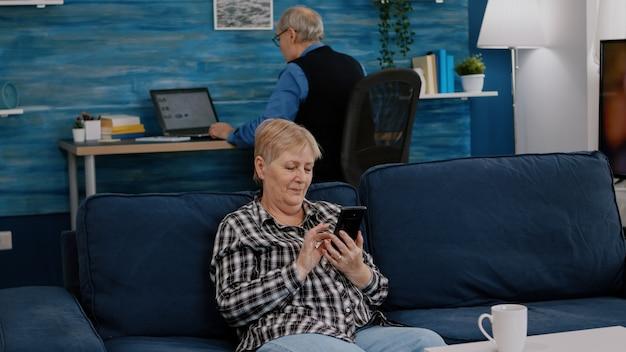 Mulher de meia idade relaxante segurando smartphone lendo e livro sentado no sofá em casa enquanto anúncio sênior.