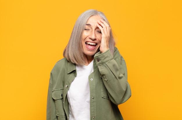 """Mulher de meia-idade rindo e batendo na testa como se dissesse dã ¢ â € âšãƒâ """"ãƒâ´oh! eu esqueci ou isso foi um erro estúpido"""