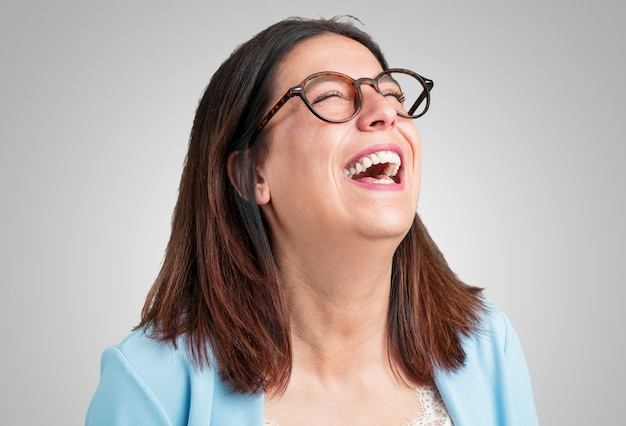 Mulher de meia idade rindo e se divertindo, sendo relaxada e alegre, se sente confiante e bem sucedida