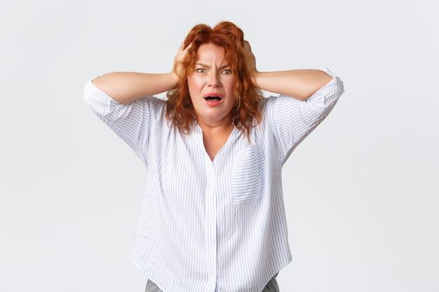 Mulher de meia-idade ruiva preocupada e frustrada agarrando a cabeça em negação