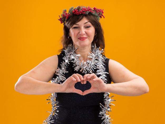 Mulher de meia-idade satisfeita com a coroa da cabeça de natal e guirlanda de ouropel em volta do pescoço, olhando para a câmera fazendo um sinal de coração isolado em fundo laranja