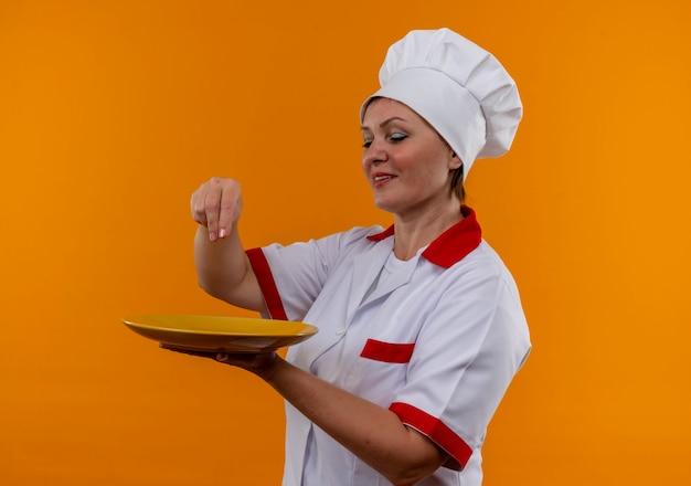 Mulher de meia-idade satisfeita com o uniforme de chef, olhando o prato na mão e fingindo que derrama sal na parede amarela isolada