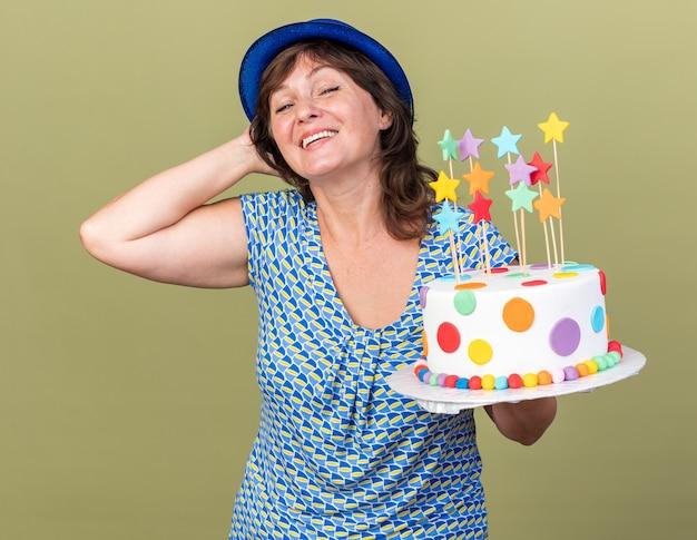 Mulher de meia-idade satisfeita com um chapéu de festa segurando um bolo de aniversário com um sorriso no rosto feliz