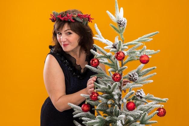 Mulher de meia-idade satisfeita com uma coroa de natal na cabeça e uma guirlanda de ouropel em volta do pescoço, atrás de uma árvore de natal decorada