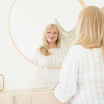 Mulher de meia-idade se olha. mulher loira linda e madura com cabelo comprido admirando reflexão