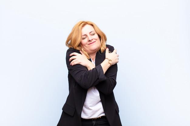 Mulher de meia idade se sentindo apaixonada, sorrindo, abraçando e se abraçando, permanecendo solteira, sendo egoísta e egocêntrica