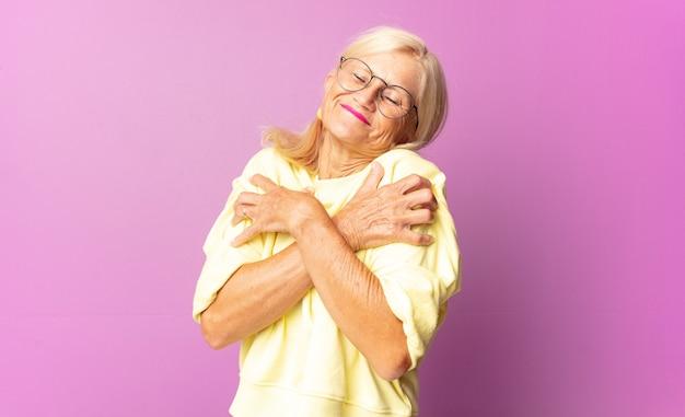 Mulher de meia-idade se sentindo apaixonada, sorrindo, acariciando e abraçando a si mesma, permanecendo solteira, sendo egoísta e egocêntrica