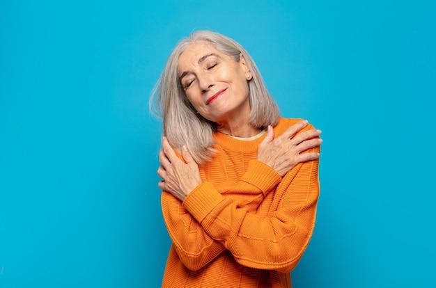 Mulher de meia-idade se sentindo apaixonada, sorrindo, acariciando e se abraçando, permanecendo solteira, sendo egoísta e egocêntrica