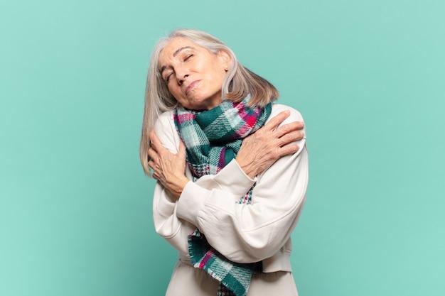Mulher de meia-idade se sentindo apaixonada, sorrindo, se abraçando e se abraçando, ficando solteira