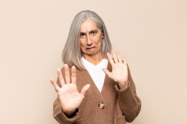 Mulher de meia-idade se sentindo apavorada, recuando e gritando de horror e pânico, reagindo a um pesadelo