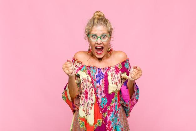 Mulher de meia-idade se sentindo chocada, animada e feliz, rindo e comemorando o sucesso, dizendo uau!