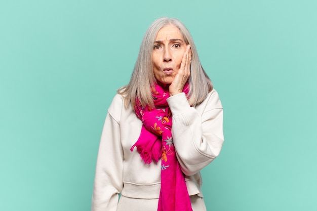 Mulher de meia-idade se sentindo chocada e atônita, segurando o rosto em descrença e sem acreditar, com a boca bem aberta