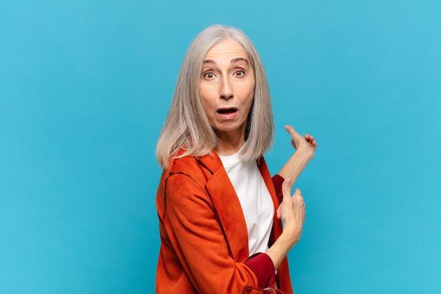 Mulher de meia-idade se sentindo chocada e surpresa, apontando para um espaço de cópia na lateral com um olhar surpreso e boquiaberto