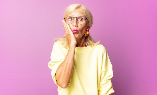 Mulher de meia-idade se sentindo chocada e surpresa, com a boca aberta e a boca aberta