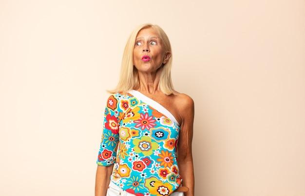 Mulher de meia idade se sentindo chocada, feliz, maravilhada e surpresa, olhando para o lado com a boca aberta