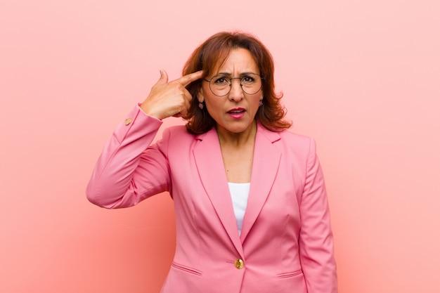 Mulher de meia idade se sentindo confusa e confusa, mostrando que você é louco, louco ou maluco na parede rosa