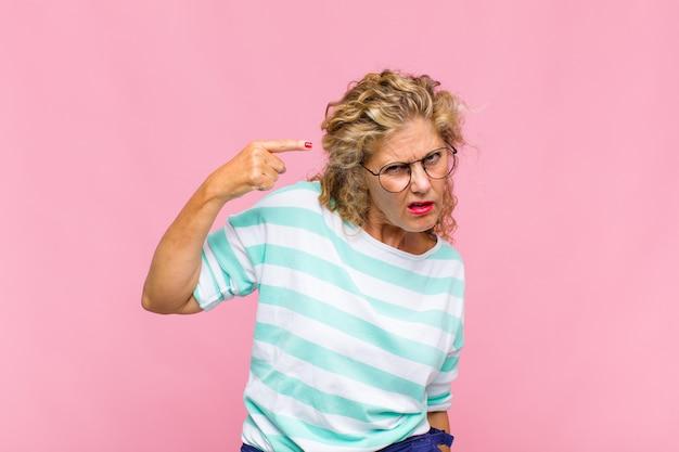 Mulher de meia-idade se sentindo confusa e perplexa, mostrando que você é louco, louco ou maluco