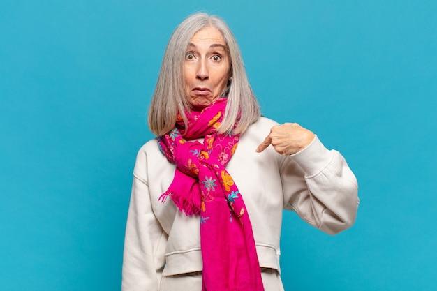 Mulher de meia-idade se sentindo confusa, intrigada e insegura, apontando para si mesma e perguntando quem, eu?