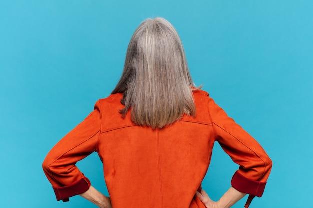 Mulher de meia idade se sentindo confusa ou cheia ou dúvidas e perguntas, imaginando, com as mãos nos quadris, retrovisor