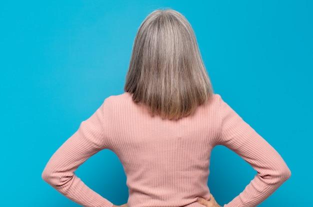 Mulher de meia-idade se sentindo confusa ou cheia ou dúvidas e perguntas, imaginando, com as mãos nos quadris, retrovisor