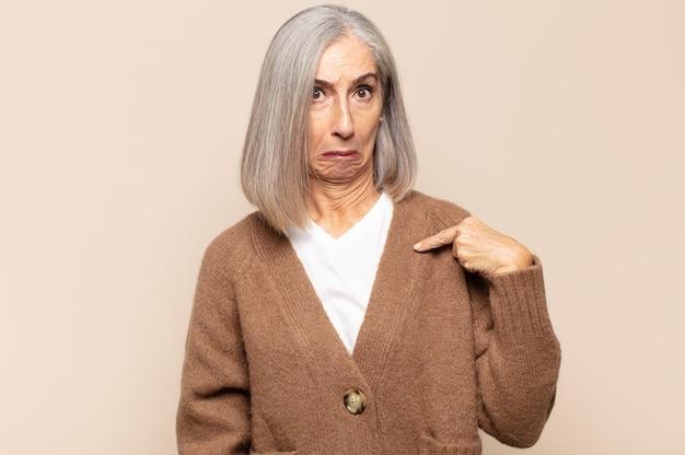 Mulher de meia-idade se sentindo confusa, perplexa e insegura, apontando para si mesma pensando e perguntando quem, eu?