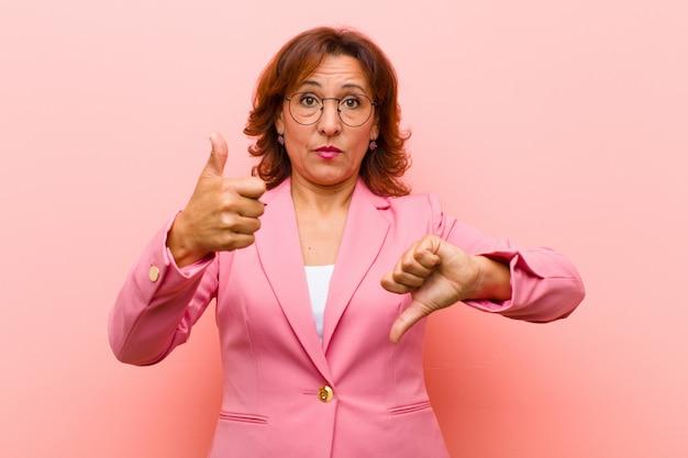 Mulher de meia idade se sentindo confusa, sem noção e insegura, ponderando o bom e o ruim em diferentes opções ou escolhas contra a parede rosa