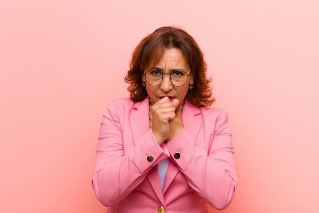 Mulher de meia idade se sentindo doente com dor de garganta e sintomas de gripe, tosse com a boca coberta contra a parede rosa