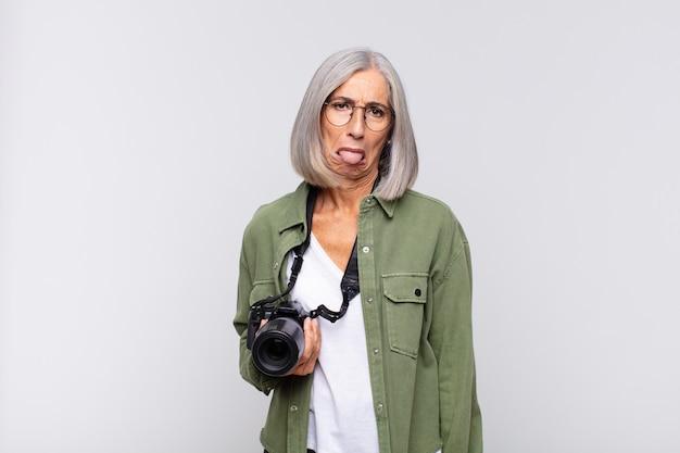 Mulher de meia-idade se sentindo enojada e irritada, mostrando a língua, não gostando de algo nojento e nojento