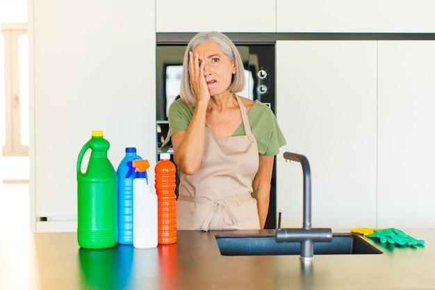 Mulher de meia idade se sentindo entediada, frustrada e com sono depois de uma tarefa cansativa, enfadonha e tediosa, segurando o rosto com a mão