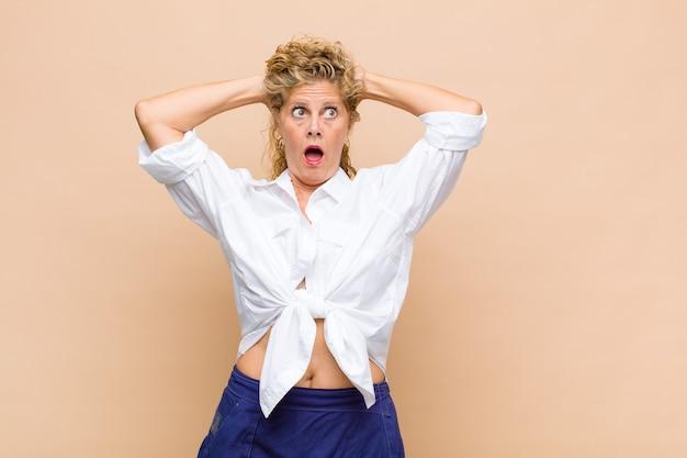 Mulher de meia idade se sentindo estressada, preocupada, ansiosa ou assustada, com as mãos na cabeça, entrando em pânico com o erro