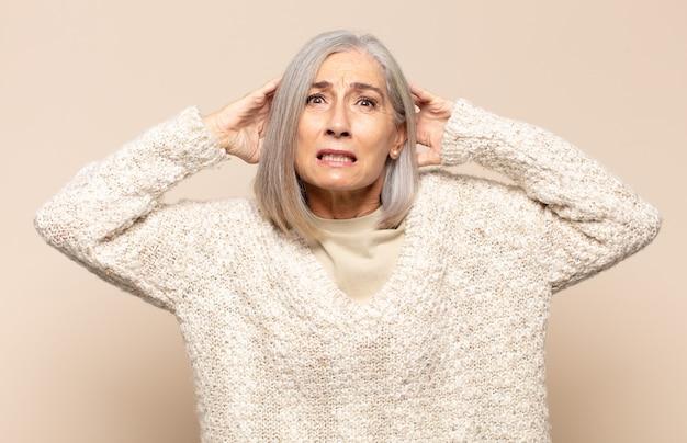 Mulher de meia-idade se sentindo estressada, preocupada, ansiosa ou com medo, com as mãos na cabeça, entrando em pânico com o erro