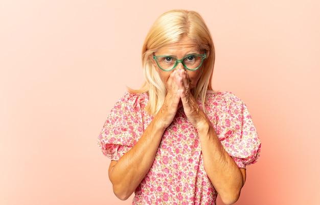 Mulher de meia-idade se sentindo feliz, amigável e positiva, sorrindo e fazendo um retrato ou moldura com as mãos