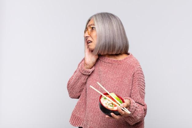 Mulher de meia-idade se sentindo feliz, animada e surpresa, olhando para o lado com as duas mãos no rosto conceito de comida asiática