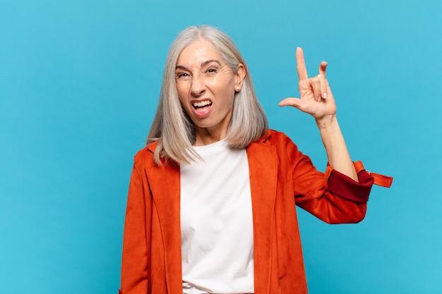 Mulher de meia-idade se sentindo feliz, divertida, confiante, positiva e rebelde, fazendo sinal de rock ou heavy metal com a mão