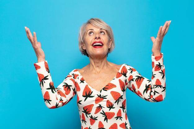 Mulher de meia-idade se sentindo feliz, maravilhada, sortuda e surpresa, comemorando a vitória com as duas mãos para cima