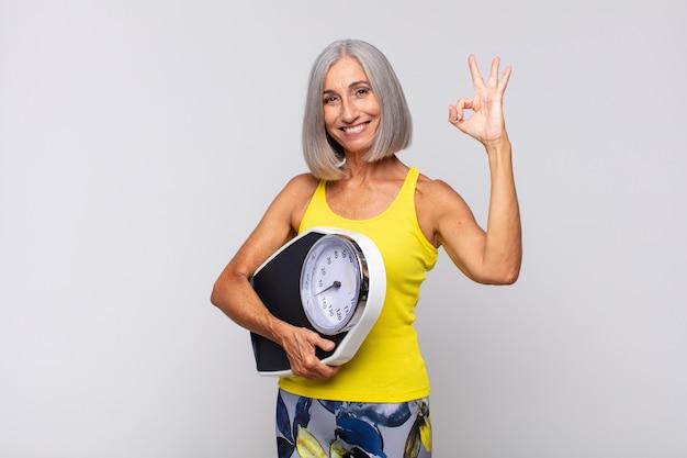 Mulher de meia idade se sentindo feliz, relaxada e satisfeita, mostrando aprovação com um gesto certo, sorrindo. conceito de fitness