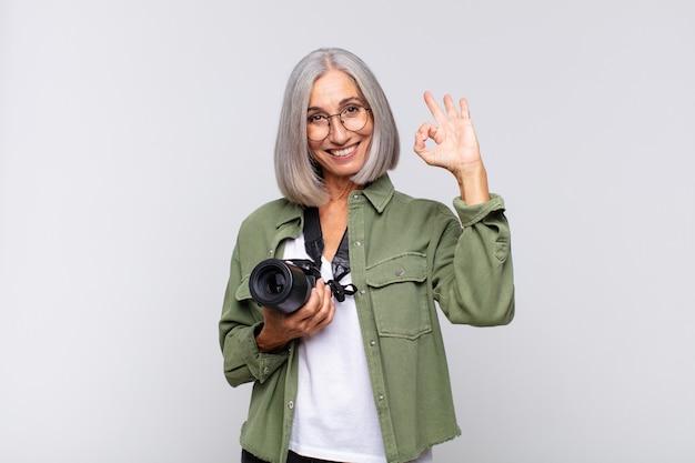 Mulher de meia idade se sentindo feliz, relaxada e satisfeita, mostrando aprovação com um gesto de ok, sorrindo