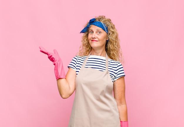 Mulher de meia-idade se sentindo feliz, surpresa e alegre, sorrindo com atitude positiva, percebendo uma solução ou ideia no conceito de dona de casa