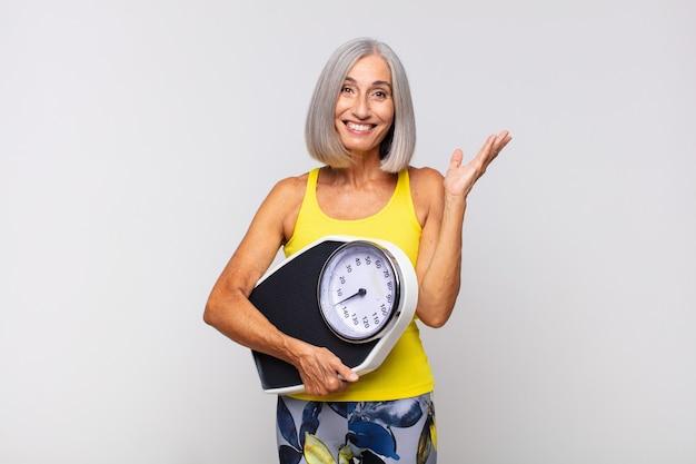 Mulher de meia-idade se sentindo feliz, surpresa e alegre, sorrindo com atitude positiva, percebendo uma solução ou ideia