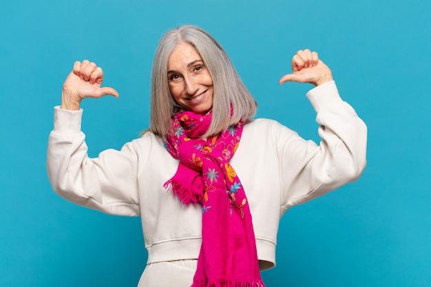 Mulher de meia-idade se sentindo orgulhosa, arrogante e confiante, parecendo satisfeita e bem-sucedida, apontando para si mesma