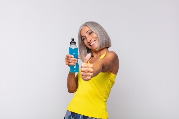 Mulher de meia idade se sentindo orgulhosa, despreocupada, confiante e feliz, sorrindo positivamente com o polegar para cima. conceito de fitness