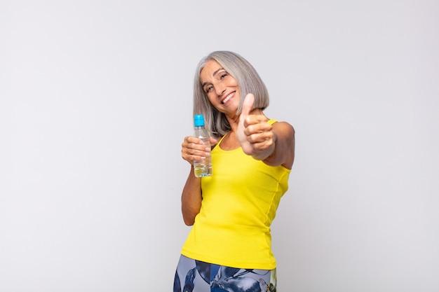 Mulher de meia idade se sentindo orgulhosa, despreocupada, confiante e feliz, sorrindo positivamente com o polegar para cima.