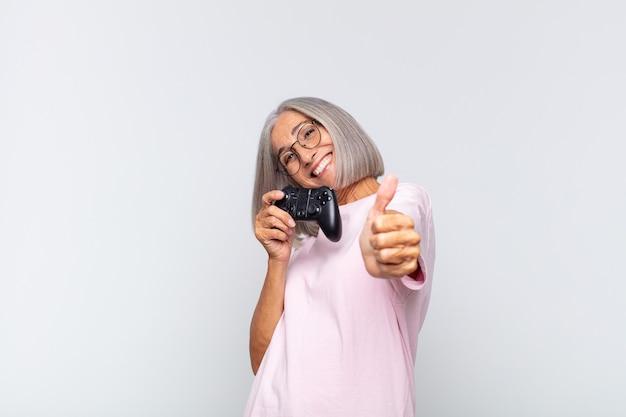Mulher de meia-idade se sentindo orgulhosa, despreocupada, confiante e feliz, sorrindo positivamente com o polegar para cima