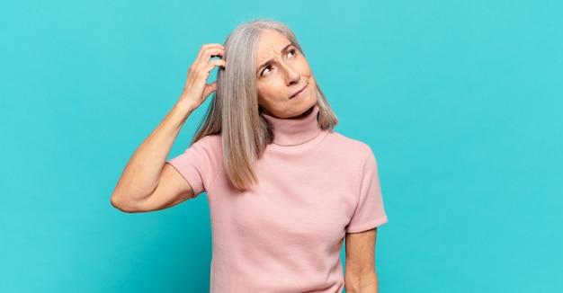 Mulher de meia-idade se sentindo perplexa e confusa, coçando a cabeça e olhando para o lado