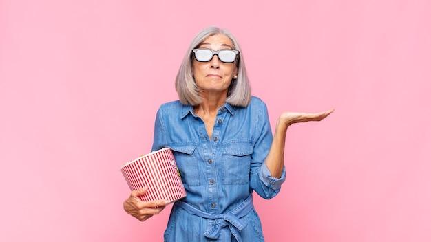 Mulher de meia-idade se sentindo perplexa e confusa, duvidando, ponderando ou escolhendo opções diferentes com o conceito de filme de expressão engraçada