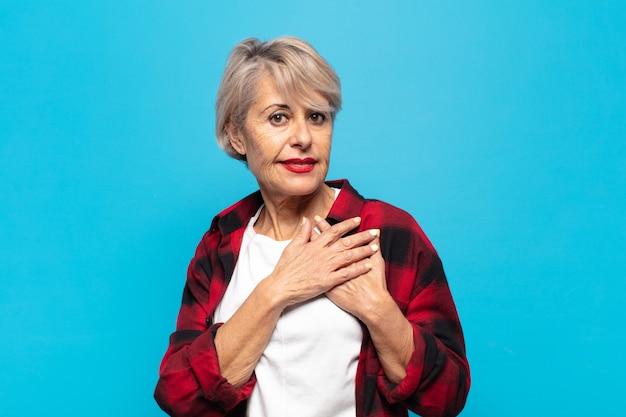 Mulher de meia-idade se sentindo romântica, feliz e apaixonada, sorrindo alegremente e segurando o coração de mãos dadas