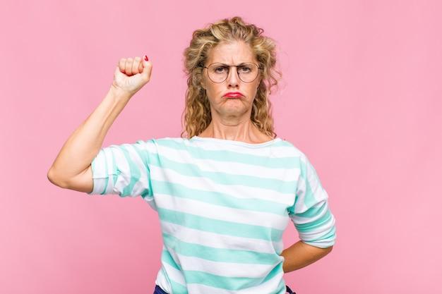 Mulher de meia-idade se sentindo séria, forte e rebelde, levantando o punho, protestando ou lutando pela revolução