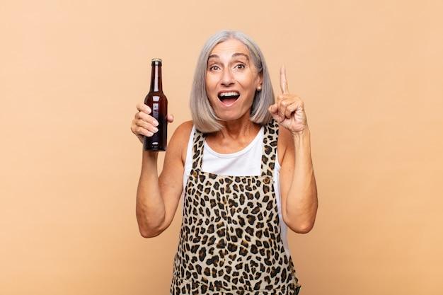 Mulher de meia-idade se sentindo um gênio feliz e animado após realizar uma ideia, levantando o dedo alegremente, eureka! com uma cerveja